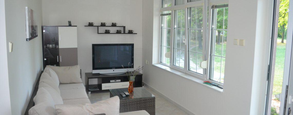 Obývacia izba s pohovkou, panoramatickým oknom a širokouhlou obrazovkou.